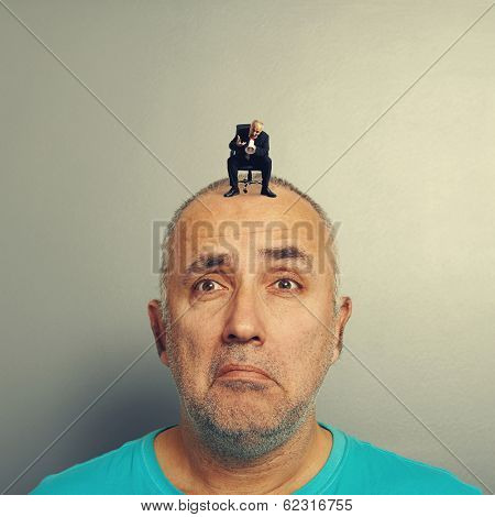 sad man with small angry businessman on his head