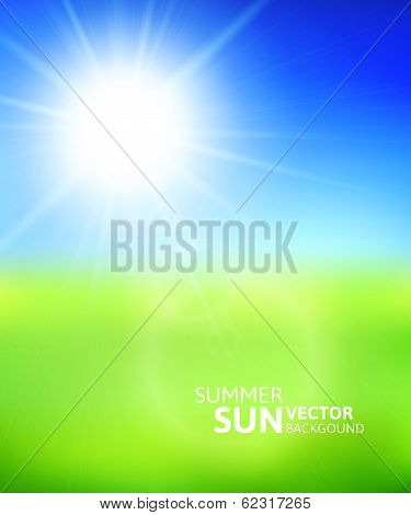 Blurry green field and blue sky with summer sun