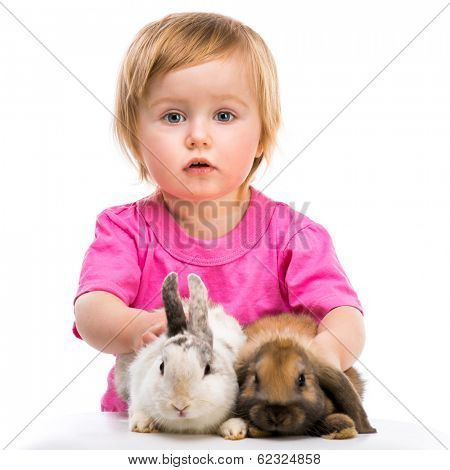 baby girl in a pink T-shirt with her small rabbits isolated on white background