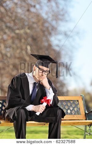 Worried graduate student sitting on a bench in park shot with tilt and shift lens