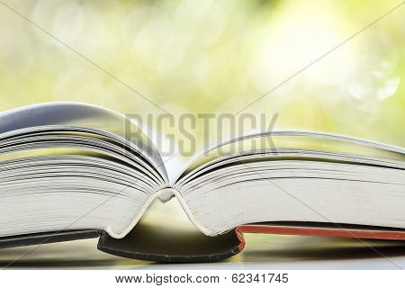 Close up on opened book against colorful bokeh background