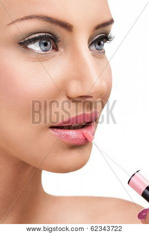 woman applying glossy on lips