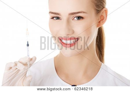 Beautiful young nurse with needle. Isolated on white.