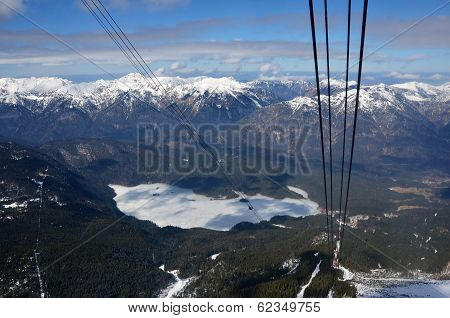 Frozen Lake And Snow-capped Mountains In The Alps