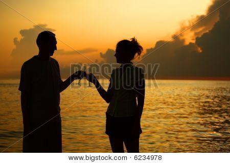 Hombre y mujer tintinean gafas. Siluetas contra el mar.