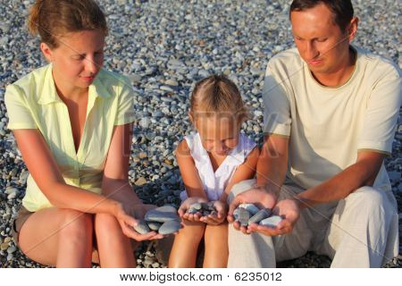 Parents and daughter sits in pebbly beach ind holding pebbles in hands