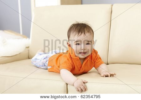 Cute baby boy lying on sofa, smiling, looking at camera.