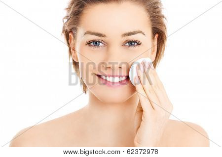 A picture of a happy woman cleaning her face with cotton pads over white background
