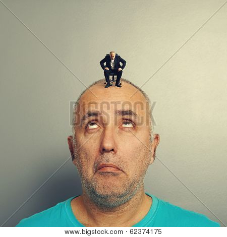 amazed man looking with misunderstanding at small businessman on his head