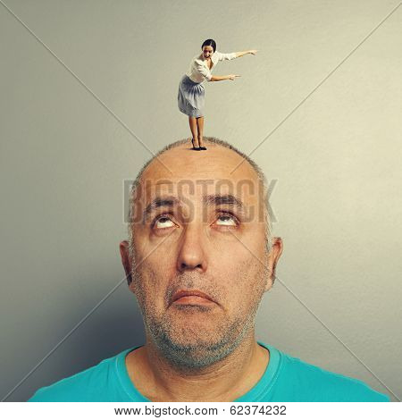 senior man looking with misunderstanding at excited woman on his head