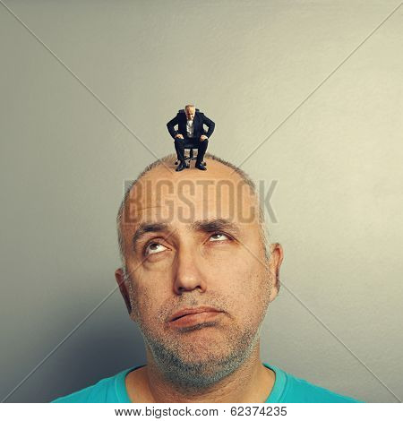 tired senior man with small businessman on his head