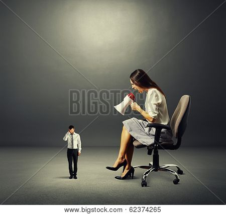 dissatisfied businesswoman and small stressed man over dark background