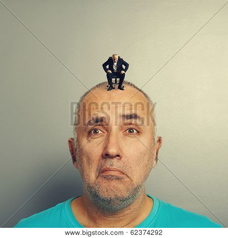 weary man with small businessman on his head over grey background