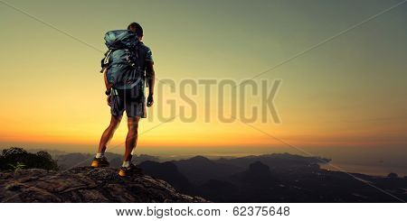 Young man hiker standing on top of the mountain completed his trek at sunrise