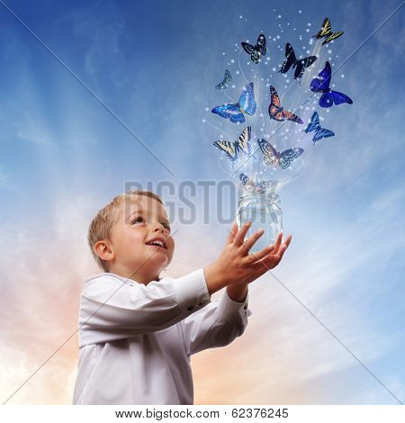 Boy releasing butterflies into the air concept for freedom, peace and spirituality