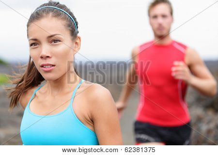 Woman runner closeup - running couple. Close up of girl jogging outside with man in background. Fit athlete couple training together outdoors. Mixed race Asian Caucasian female fitness model.