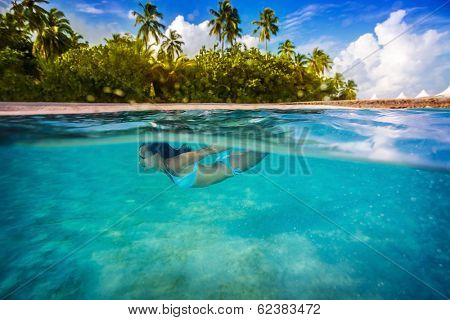 Woman swimming underwater, enjoying transparent sea and tropical nature of island, active lifestyle, summertime adventure, spending vacation in blue lagoon