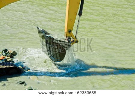 excavator machine during earthmoving in a river, logos removed