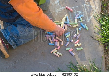 Child Draws With Crayons On The Pavement