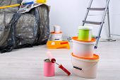 Buckets with paint, wrapped sofa and ladder on wall background. Conceptual photo of repairing works