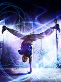 Young man break dance on wall background. With light effects.