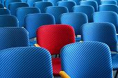 stock photo of hook  - Red seat as an eyecatcher in the middle of rows of empty blue seats conceptual image - JPG