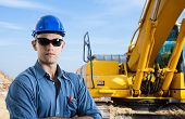 stock photo of power-shovel  - Man at work in a construction site - JPG