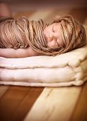 Portrait of sweet newborn baby girl sleeping, wrapped in stylish brown scarf, peaceful nap, happy ch
