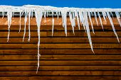 stock photo of icicle  - Icicles hanging from a wooden roof in winter - JPG