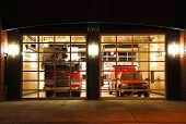 foto of firehouse  - Modern fire station at night with fire apparatus - JPG