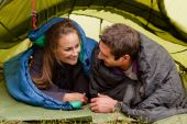 stock photo of sleeping bag  - A happy couple in a tent looking at each other - JPG