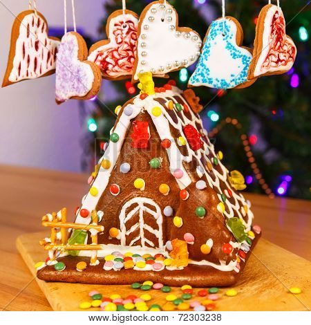 Gingerbread House With Christmas Tree And Lights On Background.