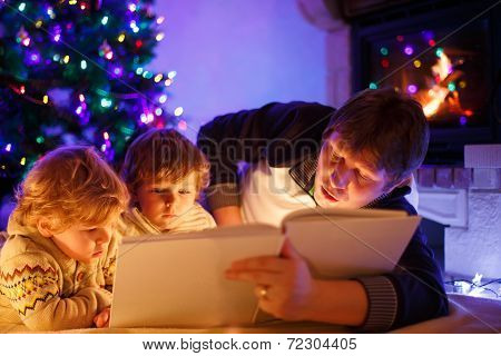Young Father And His Little Sons Reading Book By A Fireplace On Christmas