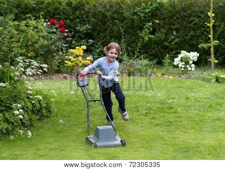 Little Boy Running With A Lawn Mower In The Garden