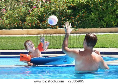 Father And Son Playing Ball In A Swimming Pool
