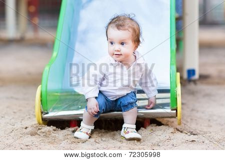 Sweet Baby Girl With Beautiful Blue Eyes Playing On A Slide