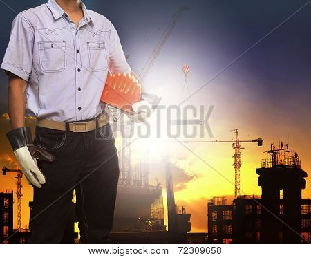 engineer man working with white safety helmet against crane and  building construction site use for