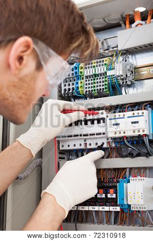 Electrical Engineer Examining Fusebox With Multimeter Probe