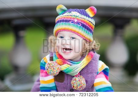 Portrait Of A Happy Toddler Girl In A Striped Colorful Knitted Hat And Scarf