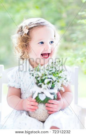 Beautiful Curly Toddler Girl In A White Dress Sitting In A White Rocking Chair Next To A Big Garden