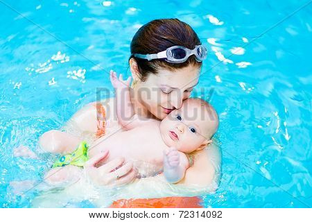 Young Mother And Her Little Baby Son Relaxing In A Swimming Pool