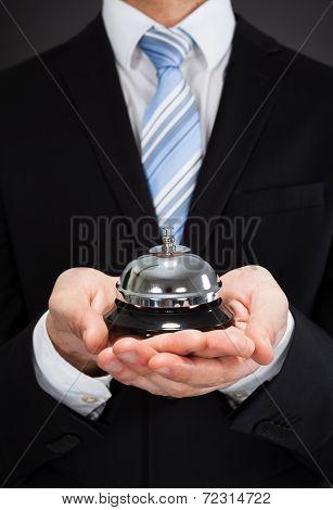 Businessman Holding Service Bell