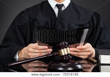 Judge Holding File With Mallet On Desk