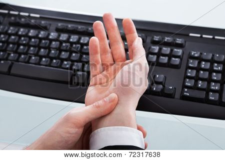 Businessman Holding Painful Wrist At Office Desk