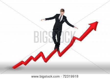 Businessman Balancing On Growing Line Graph