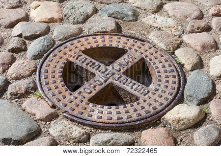 Old Steel Sewer Manhole On The Cobblestone Road. Text On Russian: Urban Sewerage