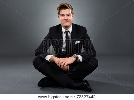 Confident Businessman Sitting Over Gray Background