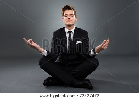 Businessman Practicing Yoga In Lotus Position