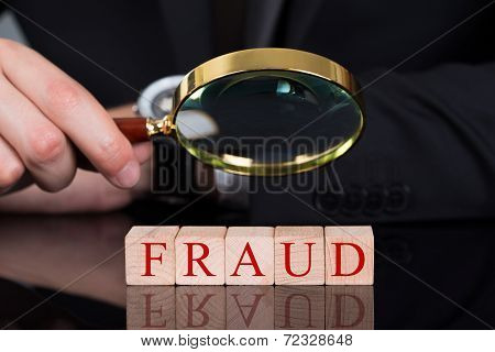 Businessman Examining Fraud Blocks Through Magnifying Glass