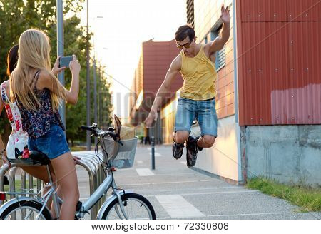 Young Man With Roller Skates Jumping And Girls Taking A Photo.